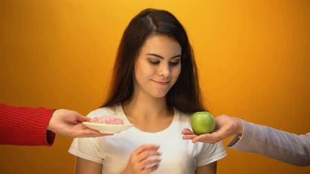 comparar : Girl eating apple instead of donut, healthy snack and vitamins vs sugary food