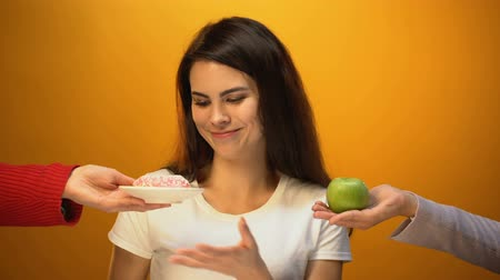 comparar : Beautiful girl eating donut instead of apple, sugar addiction, unhealthy snack Vídeos