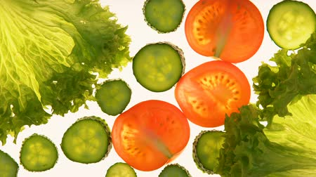 flat lay : Sliced cucumber, tomatoes and lettuce on white background, healthy vitamin diet Stock Footage