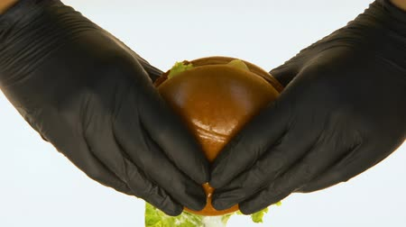 кусаться : Hands in black gloves taking greasy burger to taste, junk food quality control Стоковые видеозаписи