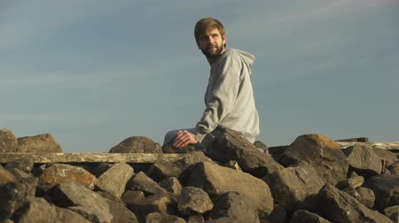 remembering : Young pensive man looking back at past, sitting on rocky hill, analyzing life Stock Footage