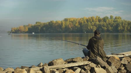 banc de poissons : Sportsman fisherman fishing in competition on river, catching fish on feeder