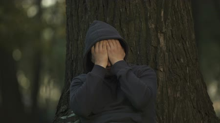 jobless : Depressed man sitting under tree in park, unemployment problem, difficulties