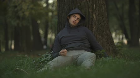 jobless : Vulnerable alcoholic sleeping under tree in park, careless and crazy youth
