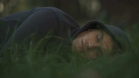 abused : Homeless male sleeping on grass in park, poverty and social issues concept