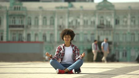 prejudice : Beautiful african-american woman practicing yoga in the city center, meditation Stock Footage