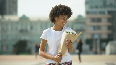 cheirando : Pleased african-american female holding bouquet and enjoying pleasant aroma