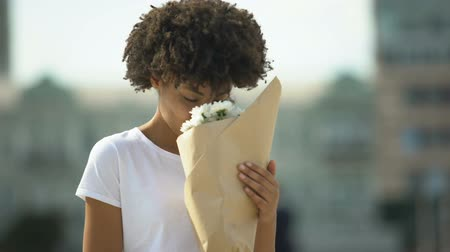 cheirando : Cute afro-american girl smiling and rejoicing beautiful bouquet from admirer