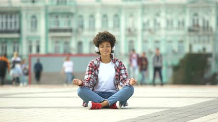 prejudice : Carefree young female sitting in lotus pose and listening to music in headphones