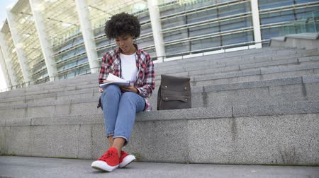curly haired : Pretty afro-american female student doing homework outdoors, smiling into camera