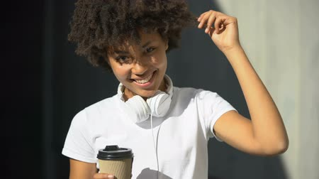buon umore : Carefree afro-american female holding cup of tea and smiling into camera, flirt
