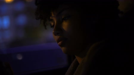 saçlı : African-american woman sitting in automobile, looking on smartphone, nighttime Stok Video