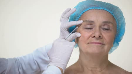 kalap : Doctor hands making facial injections for aging female patient, dermatology Stock mozgókép