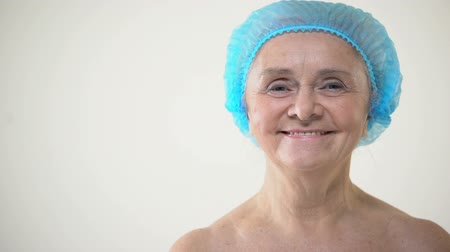 kalap : Smiling elderly female in protective hat looking to camera, plastic surgery