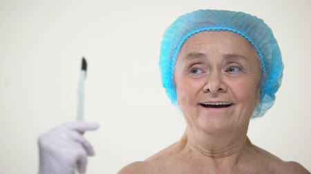 scalpel : Smiling elderly lady scared of surgical scalpel, treatment fear, plastic surgery