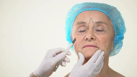 scalpel : Surgeon placing scalpel to aging female patient face with marks, face lifting Stock Footage