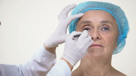 scalpel : Plastic surgeon preparing old lady for facelift operation, anti-aging therapy