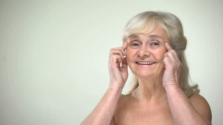 cuidados com a pele : Attractive elderly lady unwrinkling, smiling to camera, aging beauty concept Stock Footage
