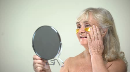 oog icoon : Joyful smiling lady applying eye patches looking in mirror, anti-aging therapy Stockvideo
