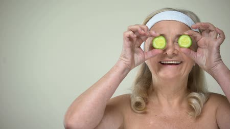 анти : Smiling elderly lady closing eyes with slices of cucumber, skincare procedures Стоковые видеозаписи