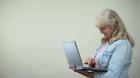 optimistický : Elderly joyful woman typing on laptop, online shopping, modern technologies