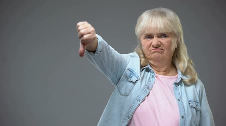 gesticulando : Unhappy aged lady showing thumbs-down gesture, unhappy with state government