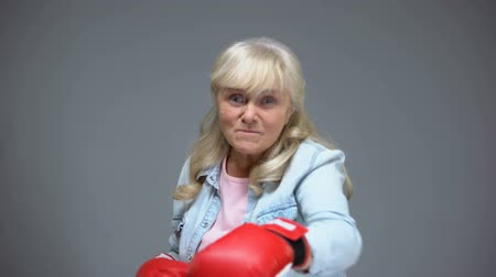self motivated : Funny childish senior lady in gloves pretending to box, self-belief concept Stock Footage