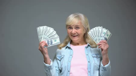 budgettering : Smiling senior woman showing dollar banknotes, quick loan service, banking
