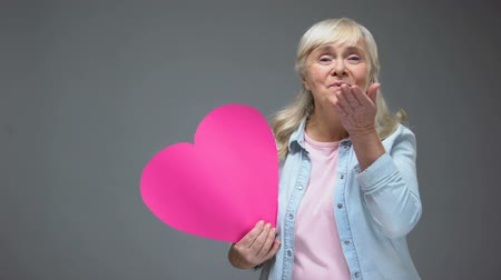 parentes : Happy elderly lady making kiss holding pink heart, Valentines day, healthcare Stock Footage