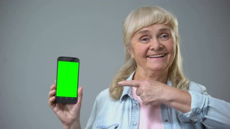 optimistický : Smiling elderly woman showing smartphone with green screen, advertisement Dostupné videozáznamy