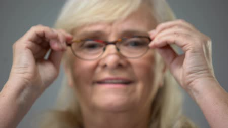 glaucoma : Happy aged lady putting on new glasses, visiting ophtalmology clinic, eyesight Stock Footage