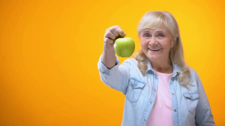 stomatologist : Smiling retiree vegetarian lady showing juicy green apple, organic food, dieting Stock Footage
