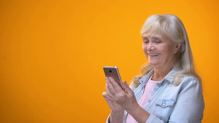 alfabetização : Smiling aged lady typing on smartphone, modern technology literacy for retirees