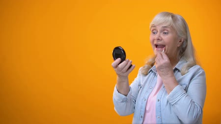 cuidados com a pele : Optimistic aged lady looking in mirror and applying lipstick dating for retirees Stock Footage