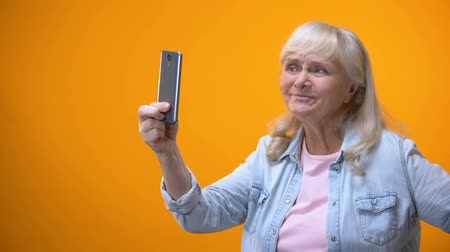 pomačkání : Optimistic senior female taking selfie on smartphone, modern technologies