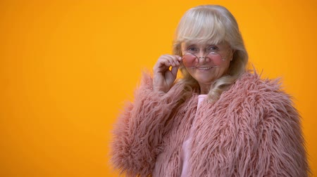 advert : Positive smiling senior lady in pink coat and round sunglasses winking, flirt