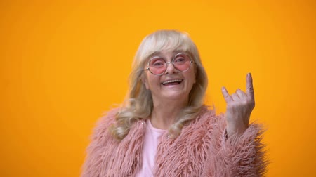 gesticulando : Joyful elderly lady in funny pink clothes making rocker gesture, positiveness