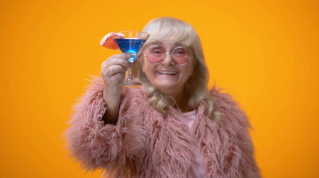advert : Cheerful elderly lady in funny pink outfit drinking blue cocktail, age positive Stock Footage