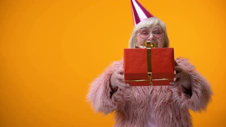kalap : Cheerful senior female in funny clothing giving birthday gift, celebration