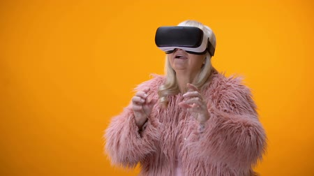optimistický : Positive senior woman in funny coat and VR headset playing video game technology