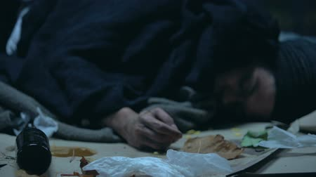 csavargó : Drunk person sleeping on cold urban street at night, alcohol abuse and addiction