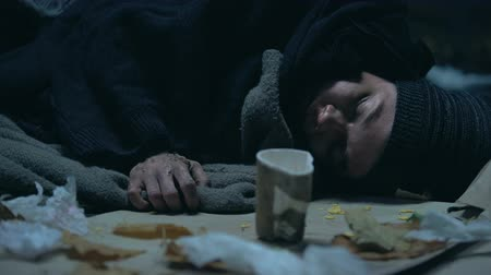 bum : Sick homeless person sleeping on cold urban street, emigration problems, shelter Stock Footage