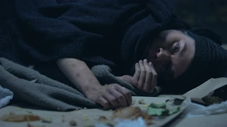 csavargó : Sick hungry homeless person lying on street and eating last piece of orts