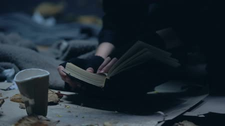 pitiable : Homeless emigrant reading bible lying on ground, hope and faith concept, praying