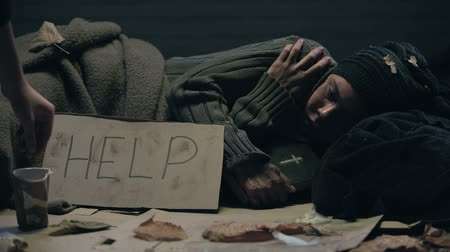 precisão : Beggar lying on street with bible, help word on cardboard, asking for charity
