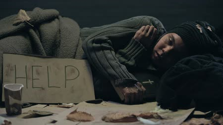 vagabundo : Crying homeless person with bible and help sign on cardboard lying on floor