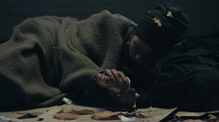 humanidade : Homeless person lying on street and counting donations, money for food, charity Stock Footage