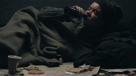 csavargó : Pity homeless person lying on floor and drinking beverage, alcohol addiction