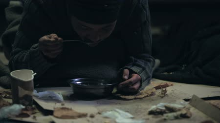 bum : Homeless person with trembling hands greedily eating soup, dirty shelter, famine Stock Footage