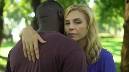 verwarring : Sad woman embraces black boyfriend, worried because of family disapproval